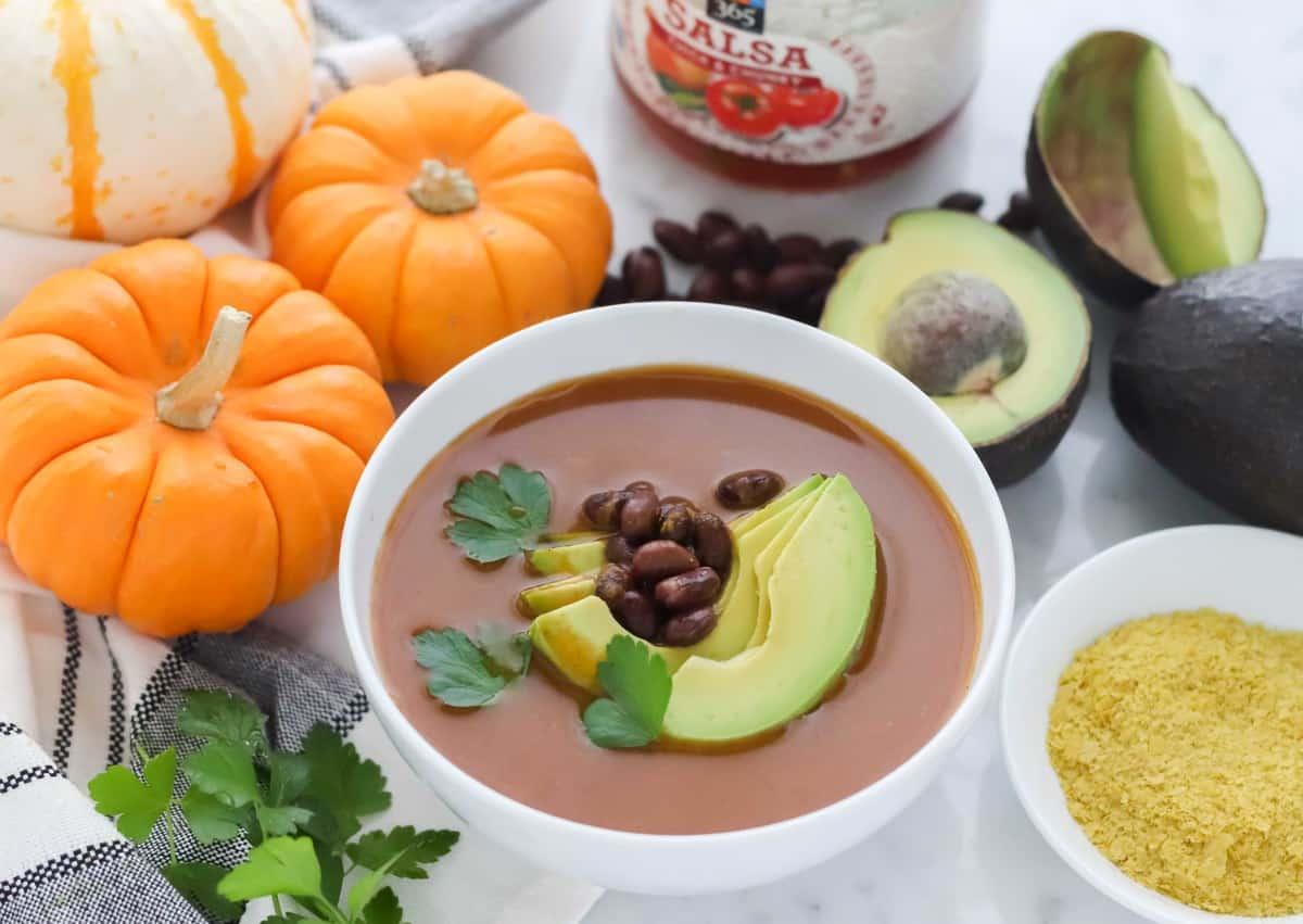 small pumpkins with bowl of salsa pumpkin soup topped with beans, cilantro, and sliced avocados
