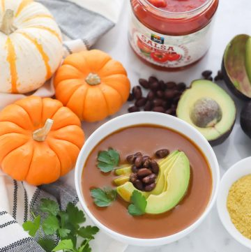 orange pumpkin, white and orange striped pumpkin, jar of salsa, avocados, black beans, bowl of pumpkin soup topped with beans, avocado and cilantro
