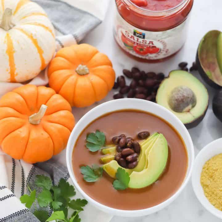 orange pumpkin, white and orange striped pumpkin, jar of salsa, avocados, black beans, bowl of pumpkin soup topped with beans, avocado and cilantro