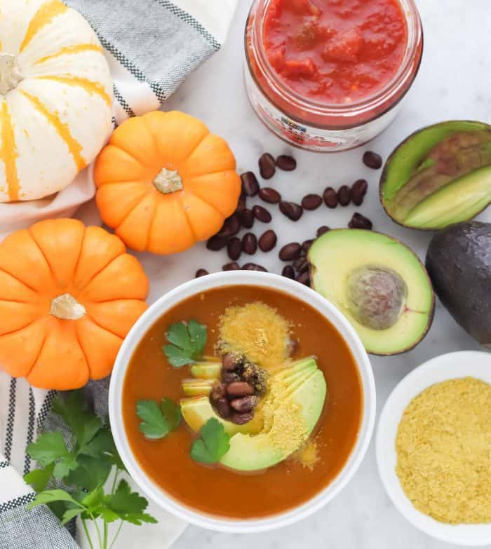 bowl of pumpkin soup topped with cilantro, avocado, and nutritional yeast with orange and white pumpkins on the side, salsa, avocado, nutritional yeast, black beans