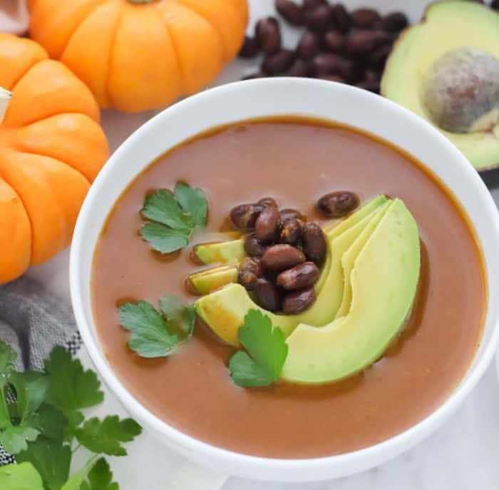 bowl of pumpkin soup topped with sliced avocado, black beans and cilantro, small pumpkins