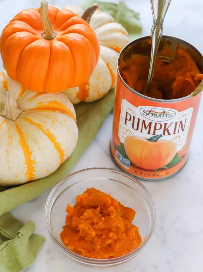 small white and orange pumpkins on green napkin, small clear bowl of pumpkin puree, can of pumpkin puree with silver spoon in it