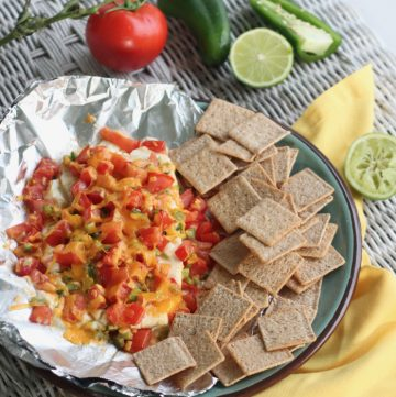 glass plate with foil topped with cream cheese appetizer and crackers on wicker table, yellow napkin and tomatoes, jalapenos and lime in background