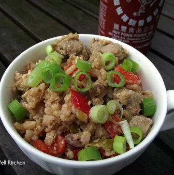 bowl of pork fried rice in a white cup with sriracha sauce