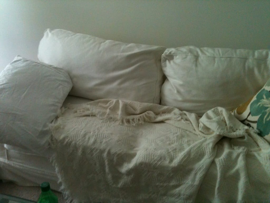 a sofa turned into a bed with a pillow and blanket