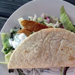 white patterned plate with fish tacos with cabbage slaw and yogurt sauce