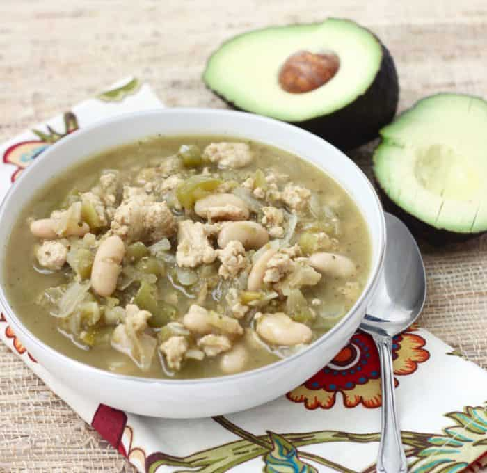 bowl of white bean and turkey chili with spoon and avocado on colorful napkin