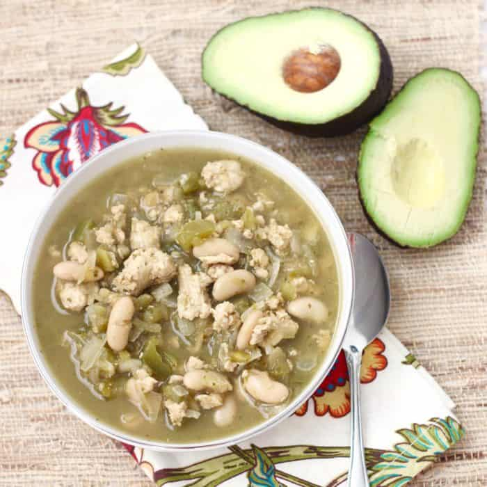 bowl of White Bean and Turkey Chili with spoon and avocado