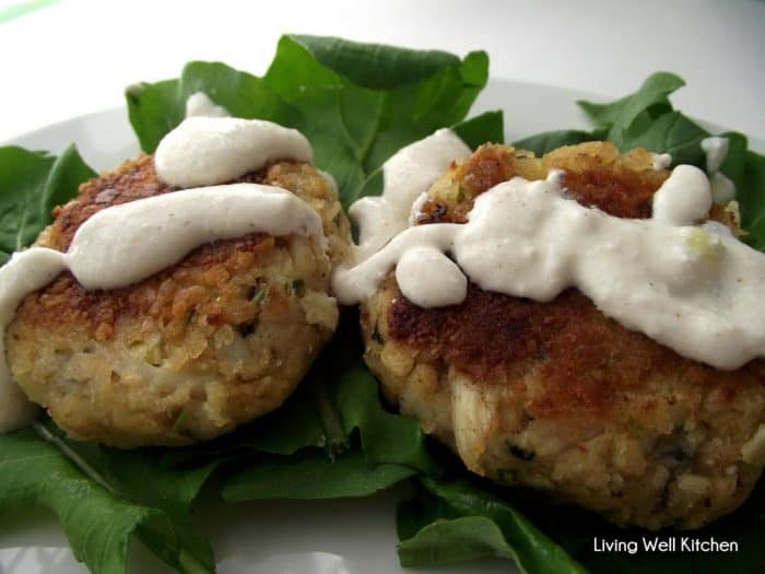 two crab cakes served on white plate with lettuce topped with sauce