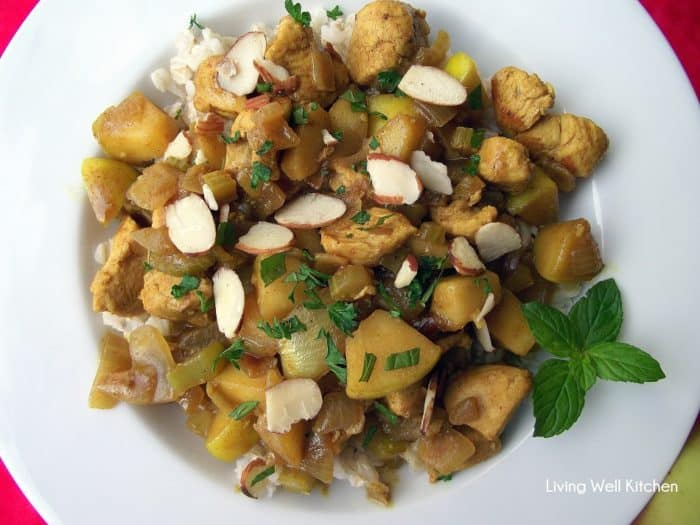 white plate with chicken curry topped with chopped almonds and mint