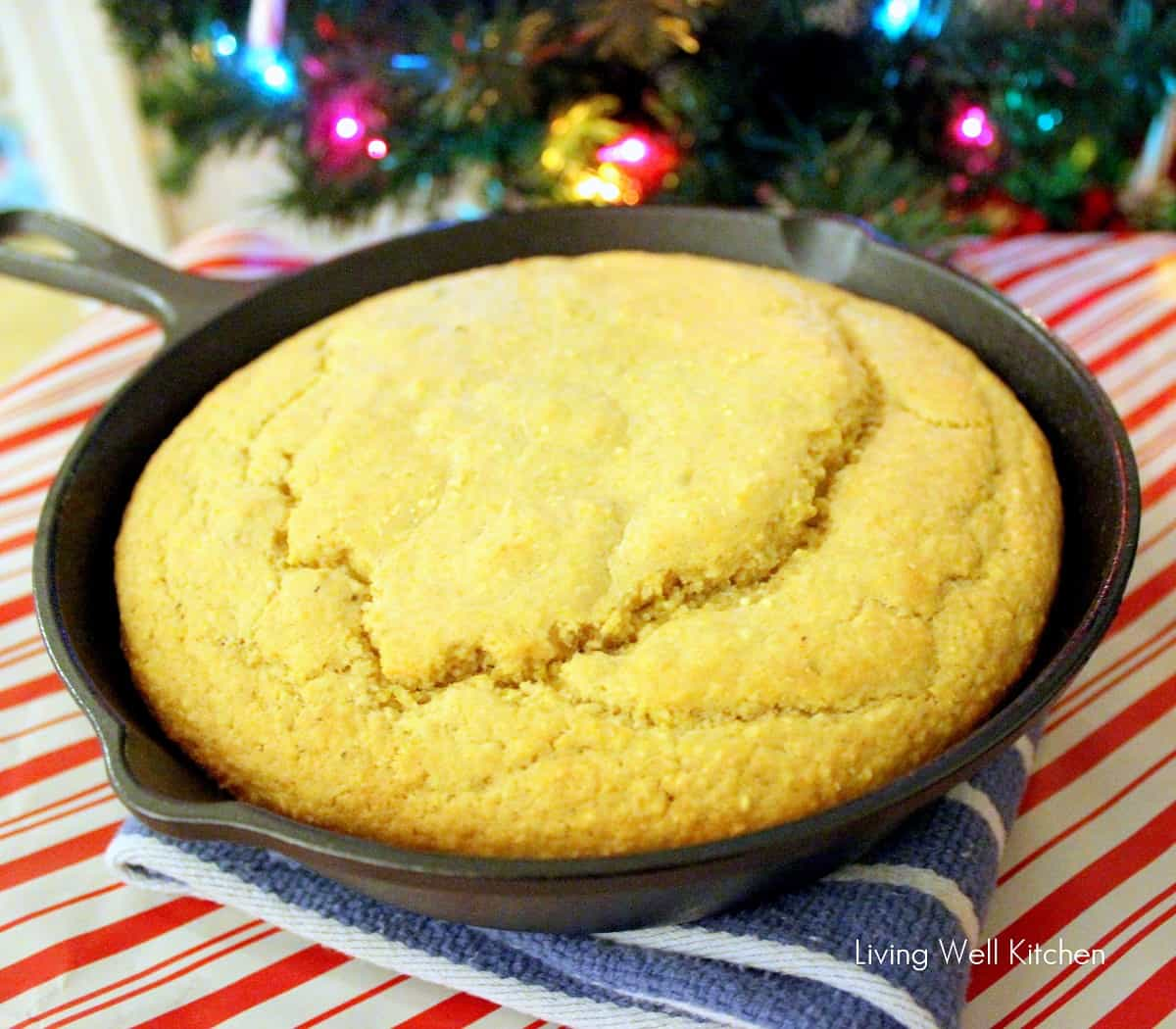Whole Grain Cornbread in cast iron skillet with Christmas tree in background