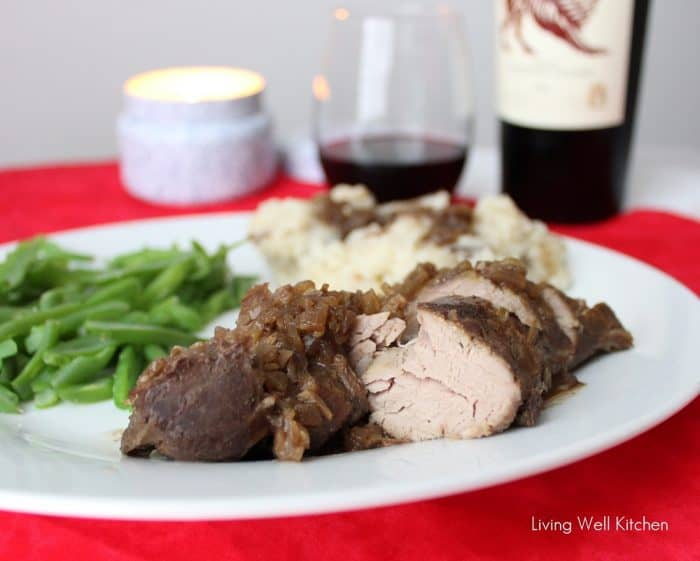 sliced Crock-Pot Pork Tenderloin and gravy with green beans and mashed potatoes on white plate on red table with candle and red wine
