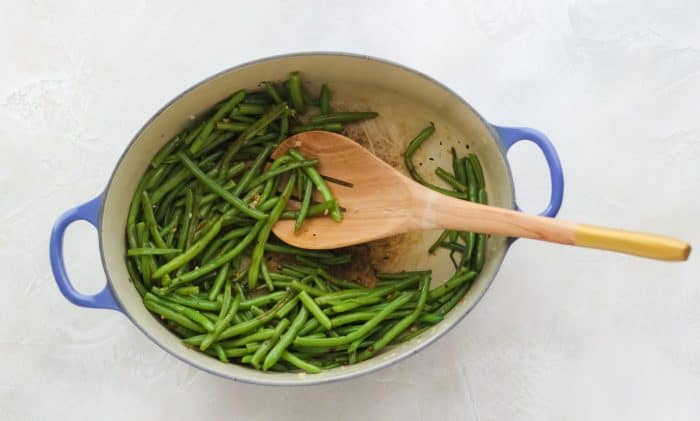 wooden spoon stirring sauteed frozen green beans in a blue pot