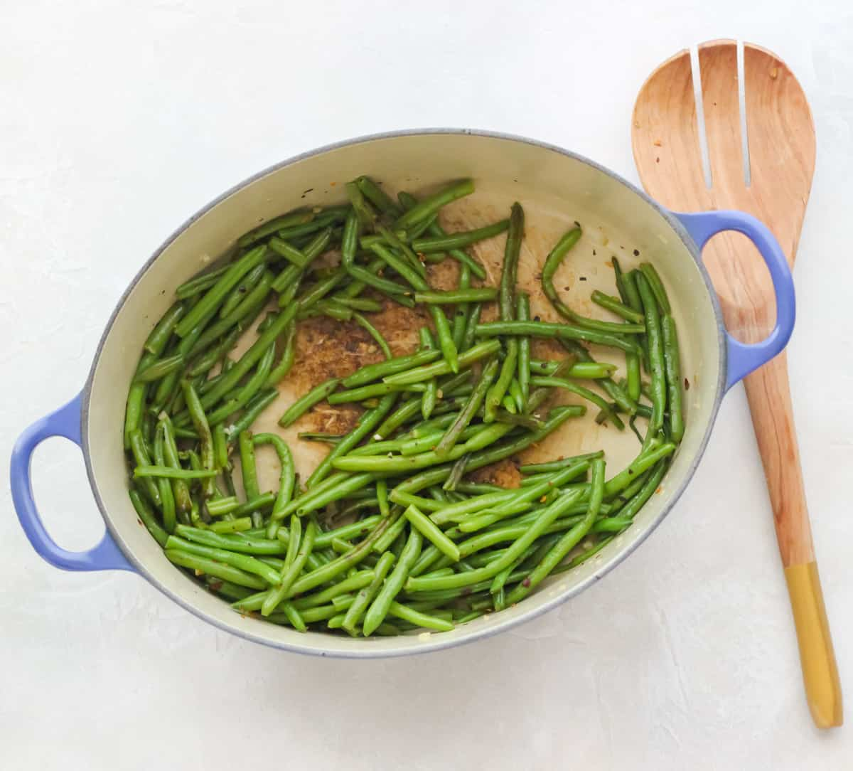 white counter with blue pot of sauteed green beans, wooden spoon resting on counter next to pot