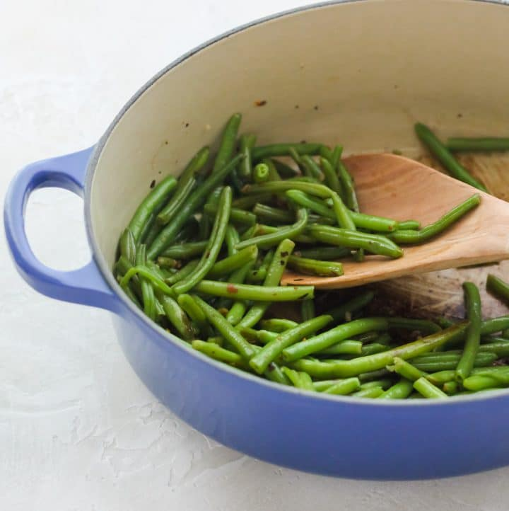 blue dutch oven with sautéed green beans and a wooden spoon