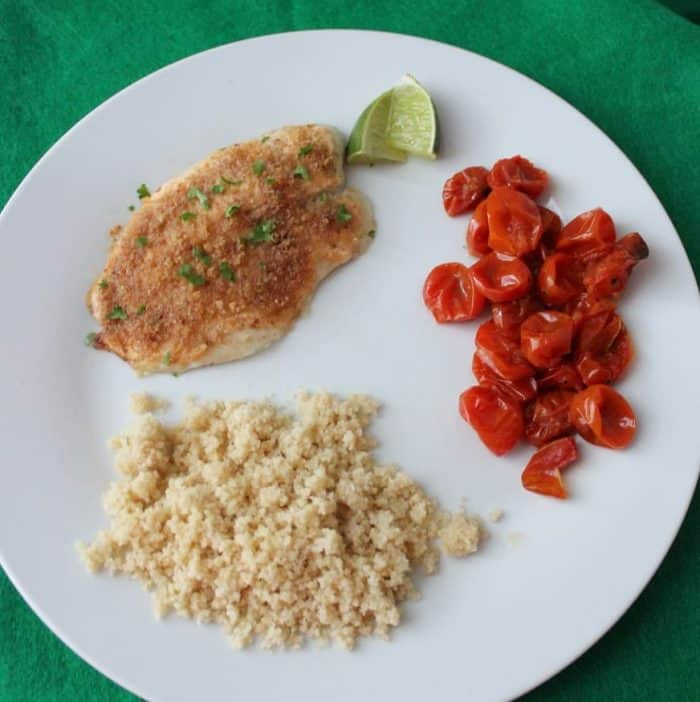 white plate of Easy Baked Fish, lime, roasted tomatoes and couscous on green table