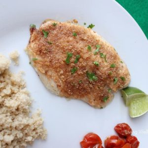 white plate on green napkin with Easy Baked Fish, lime slice, tomatoes and couscous