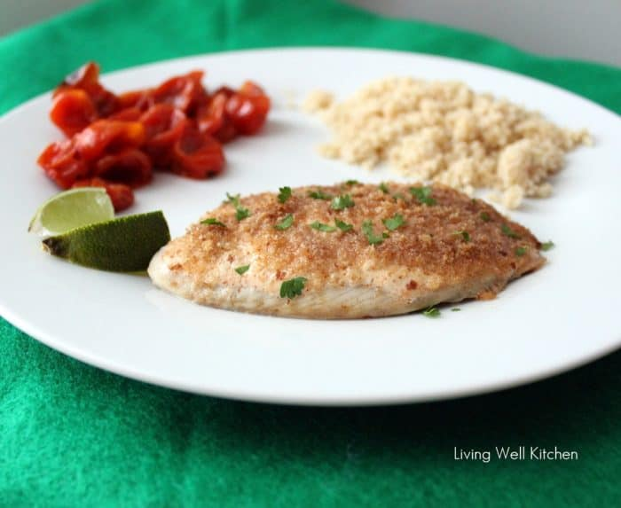 white plate with Easy Baked Fish, lime slice, couscous, and roasted tomatoes