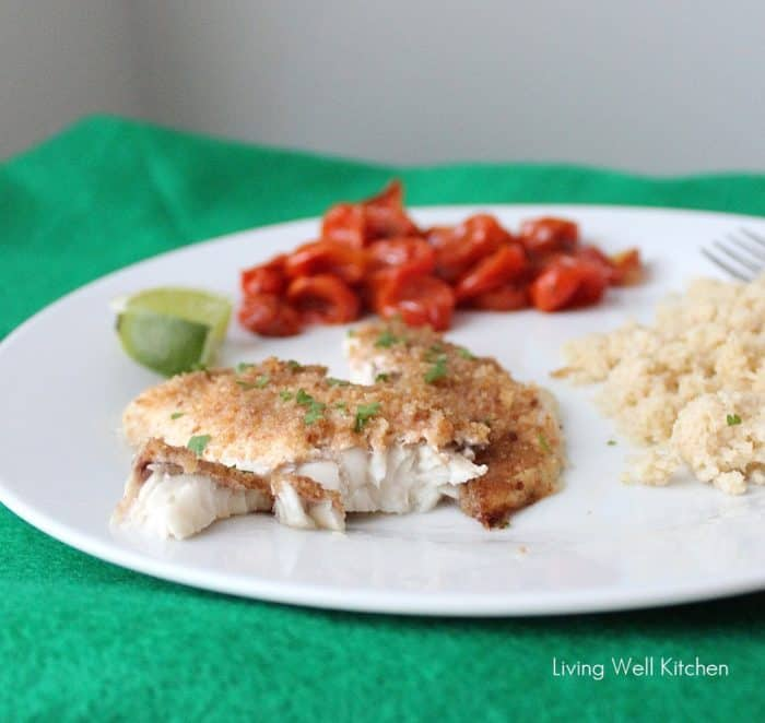 green placemat with white plate of flaked baked fish, couscous, tomatoes and lime slice