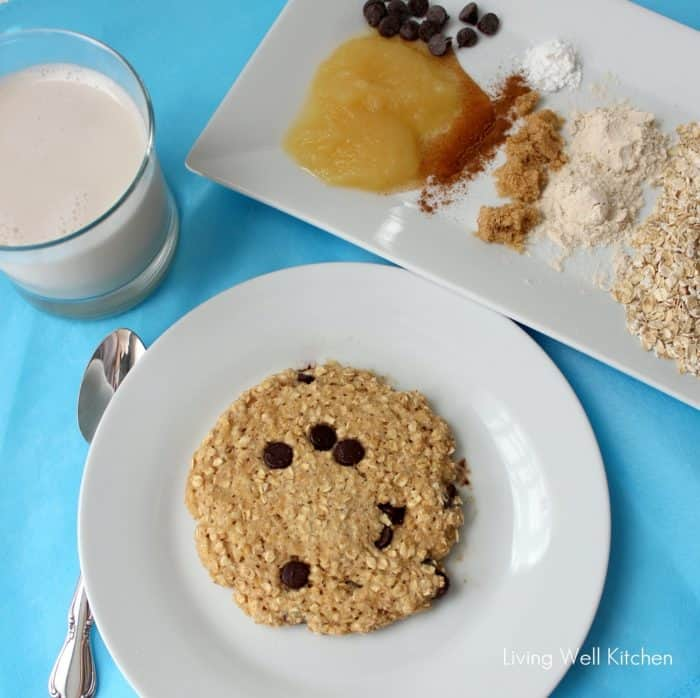 cookie on a white plate on blue table cloth, glass of milk, plate of ingredients