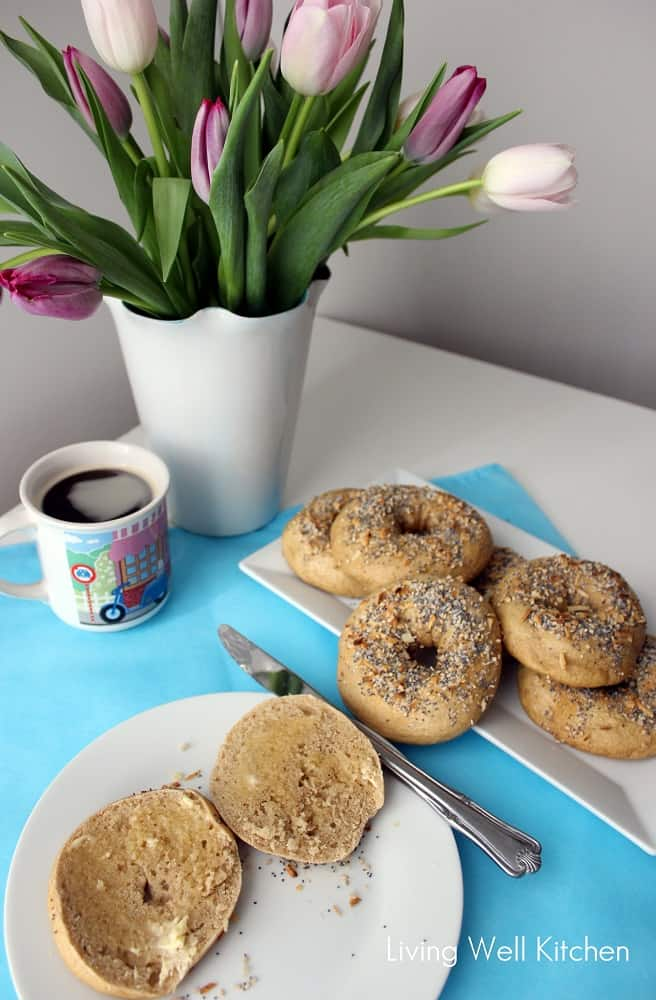 plate of Everything Bagels and one cut open covered in butter with a mug of coffee on a blue placemat and a vase of flowers