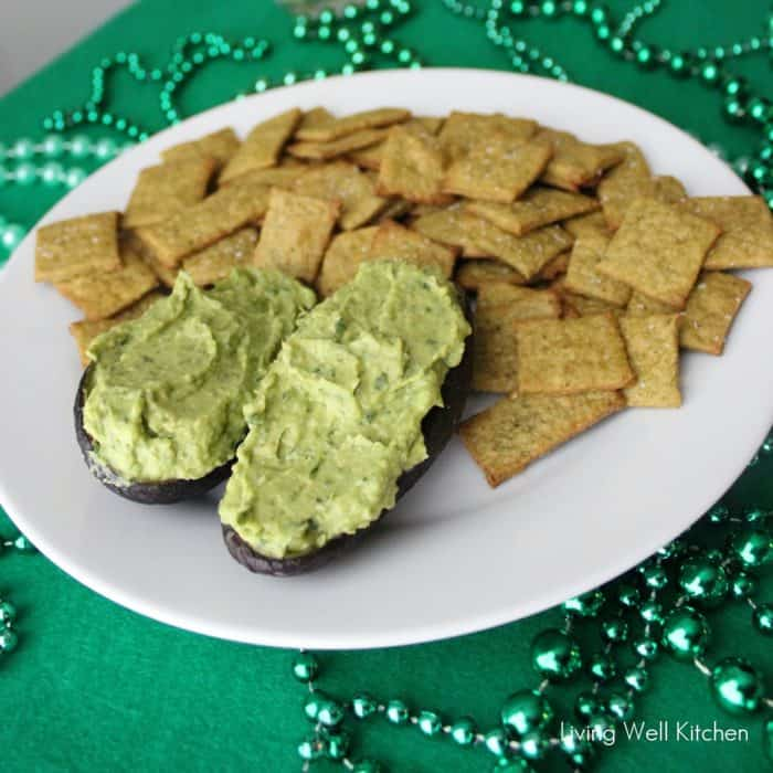 Spinach and Avocado Hummus in avocado skin with plate of homemade crackers on green tablecloth with green beads