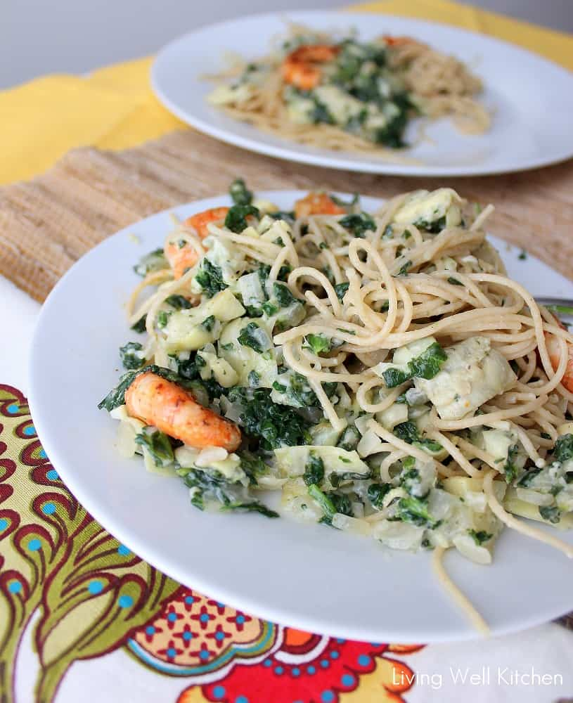 Pasta covered in a rich and creamy spinach artichoke sauce, topped with shrimp that's deliciously satisfying