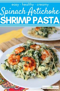shrimp on top of pasta covered in spinach artichoke sauce