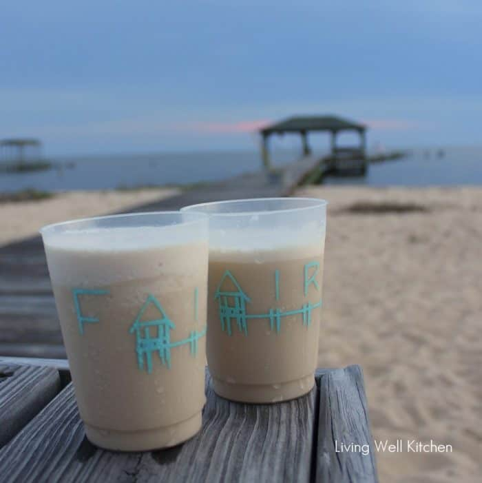 two bushwacker cocktails in Fairhope plastic cups on wooden pier with sand and water in background