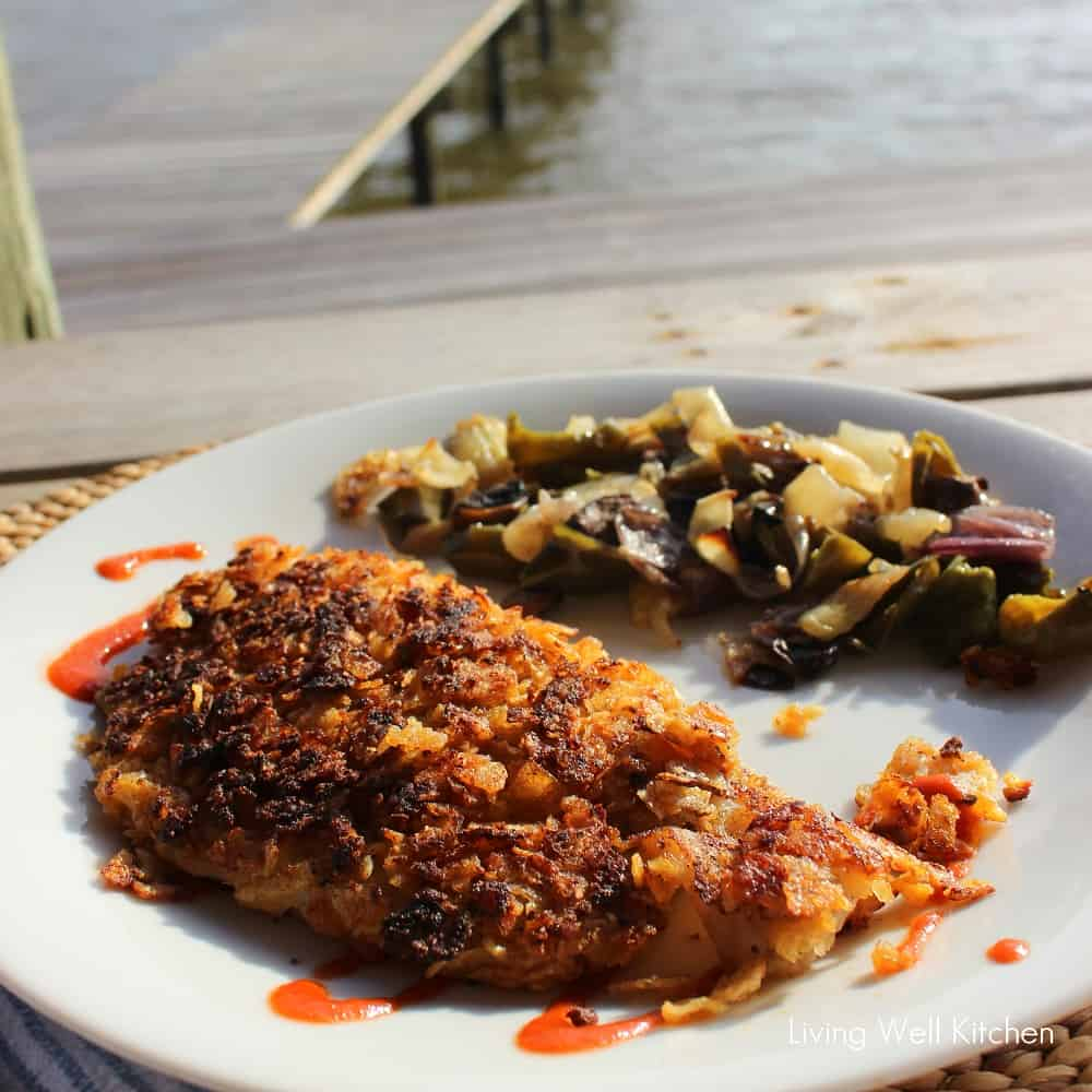 potato chip crusted fish with hot sauce, roasted veggies on wooden table with water in the background
