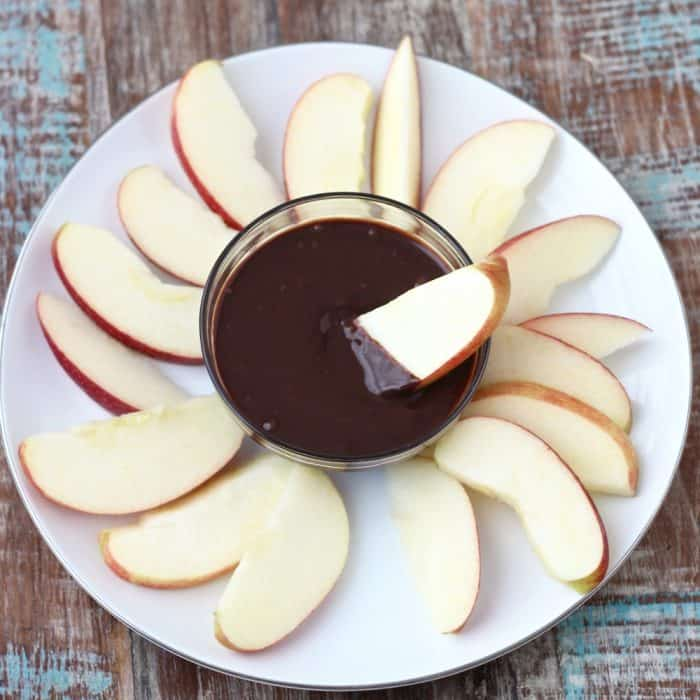 apple slice dipping into a bowl of chocolate sauce on a white plate full of apples