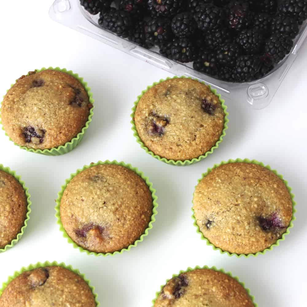 Blackberry Almond Muffins in green muffin liners with fresh blackberries