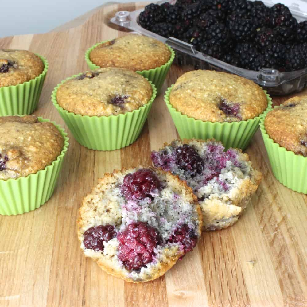 wooden cutting board with Blackberry Almond Muffins and one open on table, fresh blackberries
