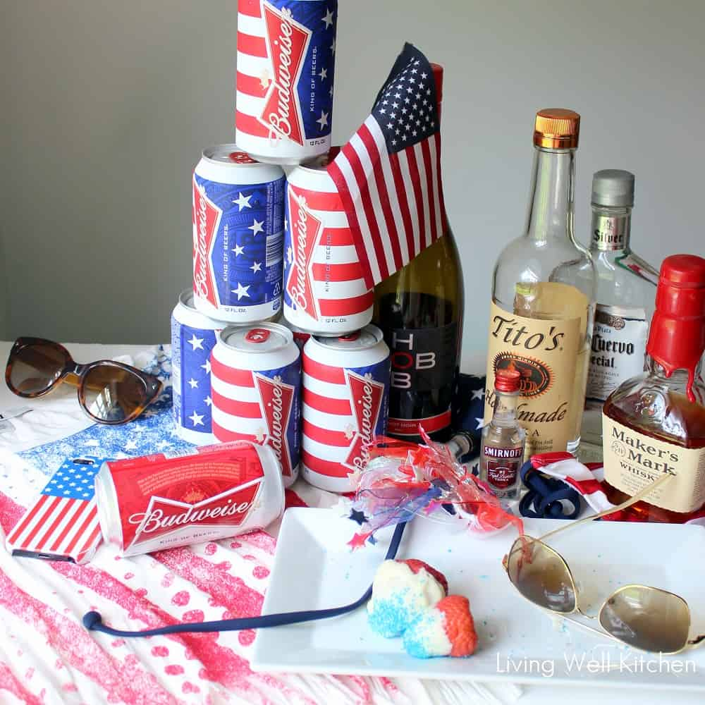 American flag tshirt with Budweiser cans, a plate of colorful strawberries, bottles of vodka, wine, tequila, and whisky with sunglasses