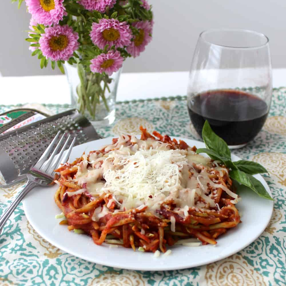 plate of Broccoli Slaw Spaghetti with cheese, wine, and flowers
