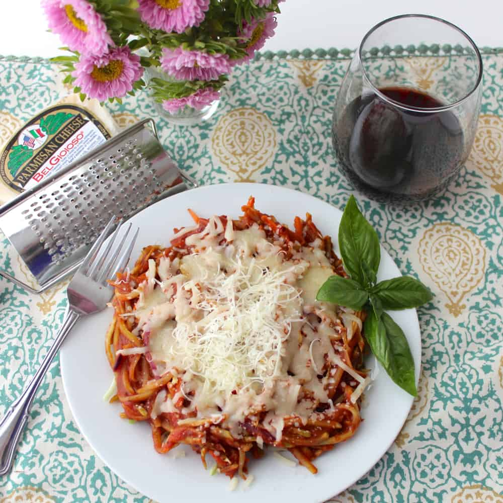 plate of Broccoli Slaw Spaghetti with cheese grater, flowers, and wine