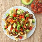 plate of nachos with avocado and salsa