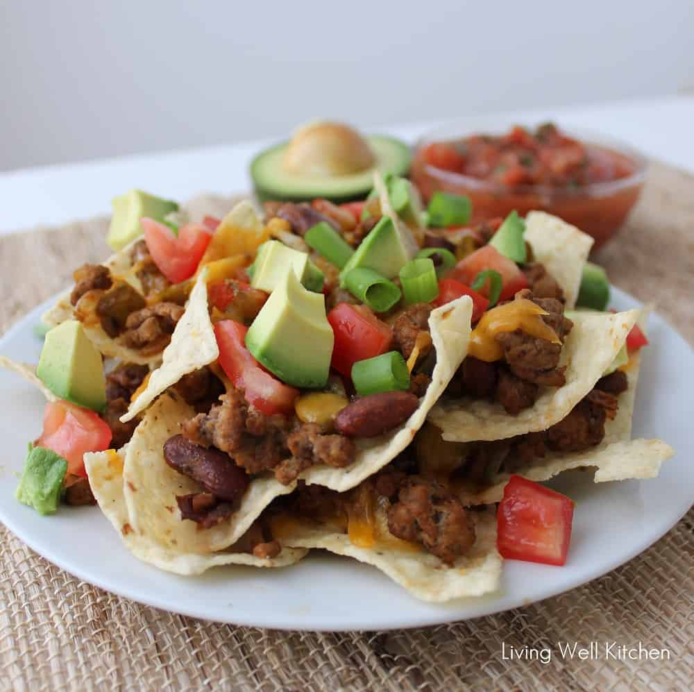 plate of Loaded Nachos with chips, beef, beans, cheese, tomatoes, avocados
