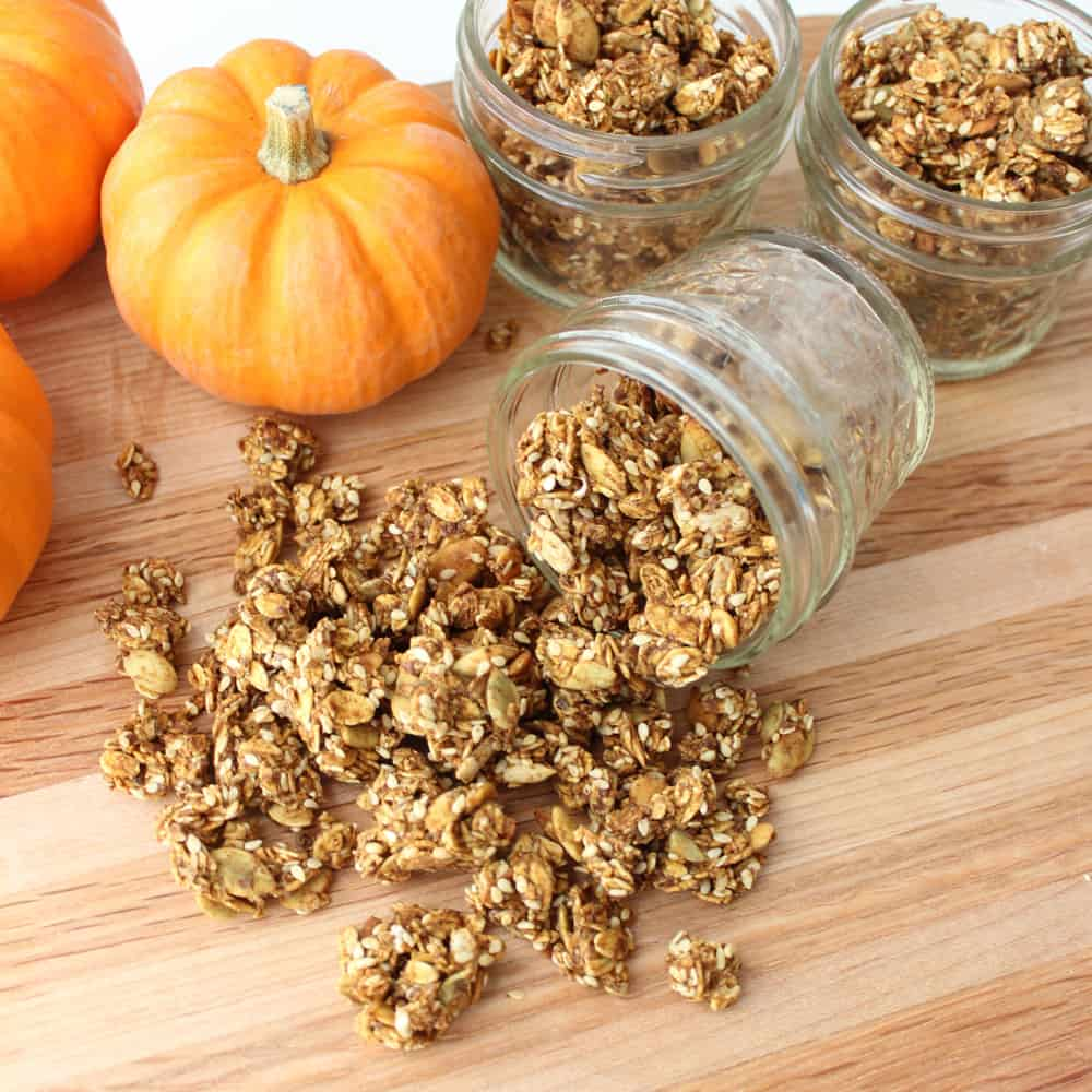 pumpkin granola spilled out of jar with mini pumpkins