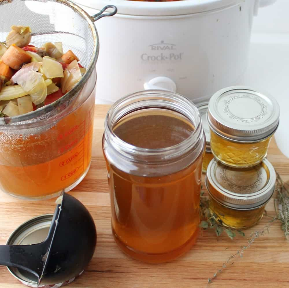 Crock-Pot Vegetable Broth in jars with drained veggie scraps and a crock pot