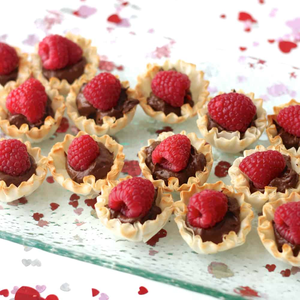 Chocolate and Raspberry Tartlets on clear platter with heart confetti