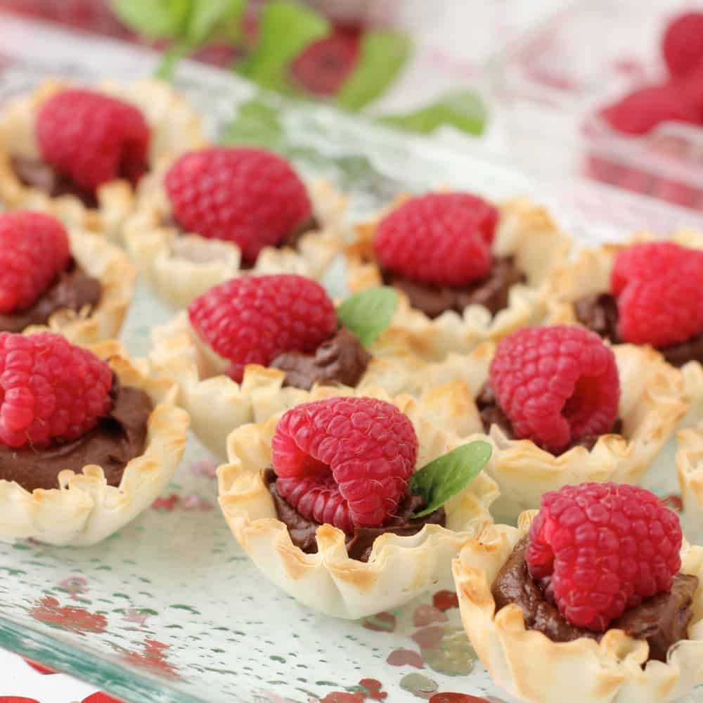 Chocolate Tartlets topped with raspberries and fresh mint