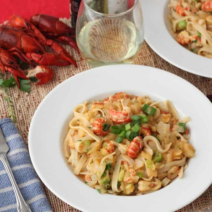 bowl of Crawfish Monica with wine and boiled crawfish