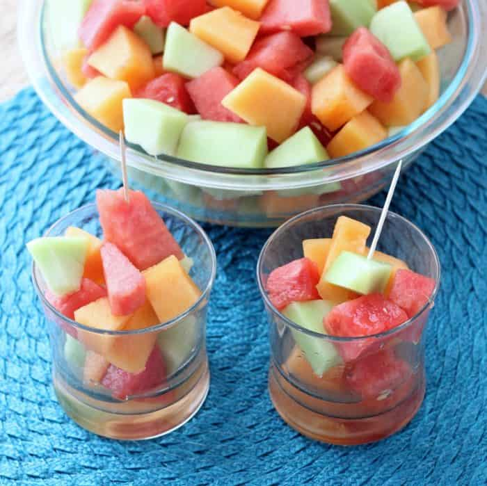 glasses with chopped watermelon, cantaloupe, and honeydew with toothpicks