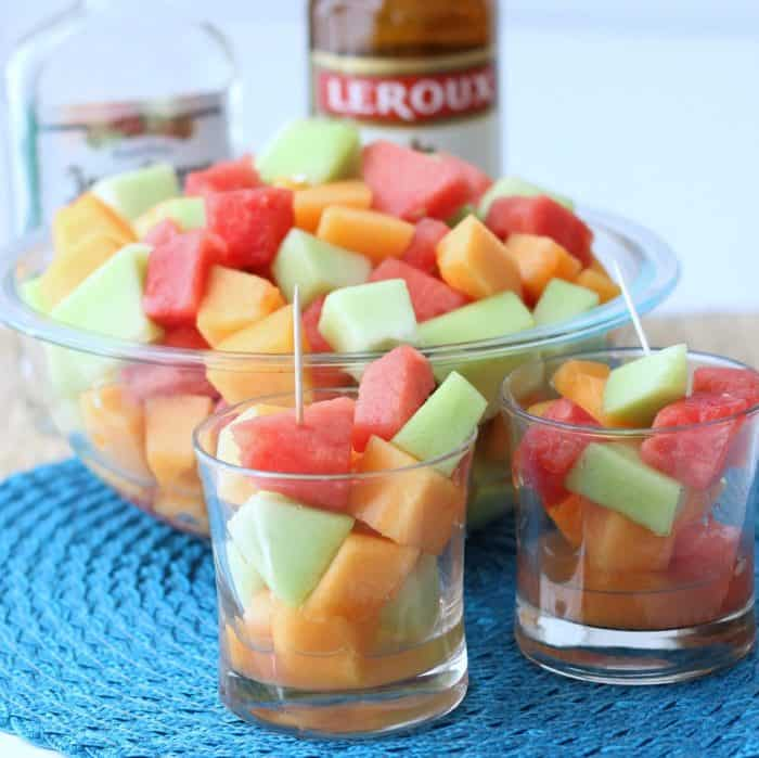 glasses with chopped watermelon, cantaloupe, and honeydew with toothpicks, tequila, triple sec