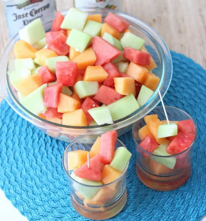 large bowl and glasses with chopped watermelon, cantaloupe, and honeydew with toothpicks