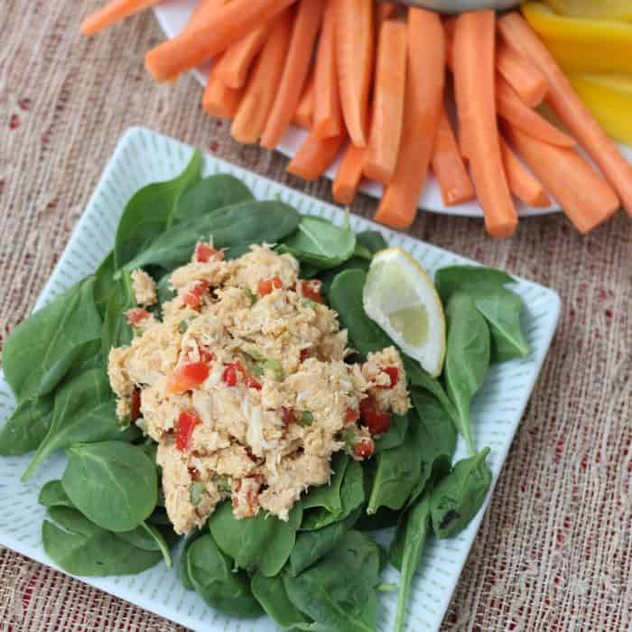 plate of spinach topped with Hummus Chicken Salad and a plate of sliced carrots