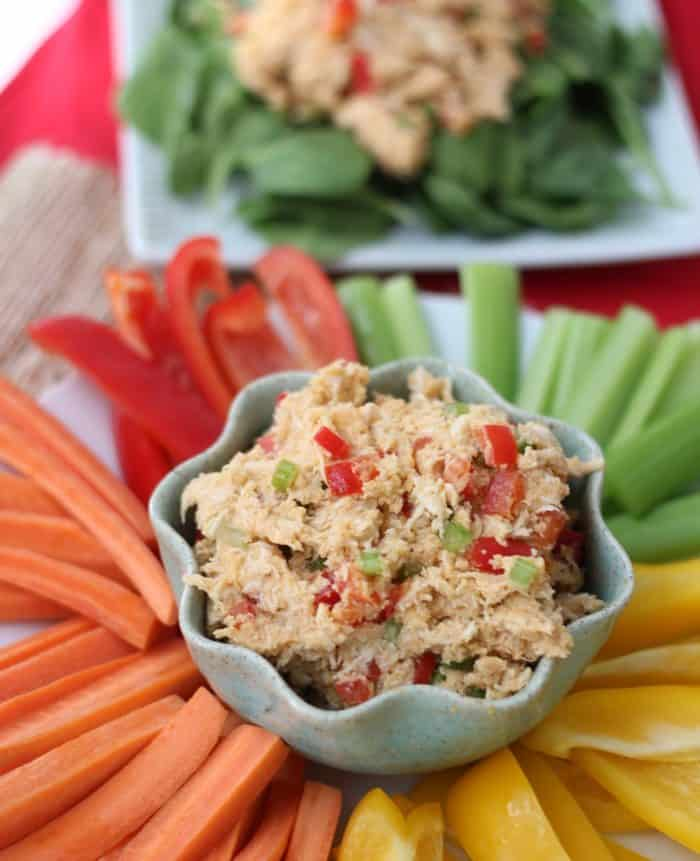 sliced carrots, yellow and red bell peppers, celery, with a blue bowl full of Hummus Chicken Salad
