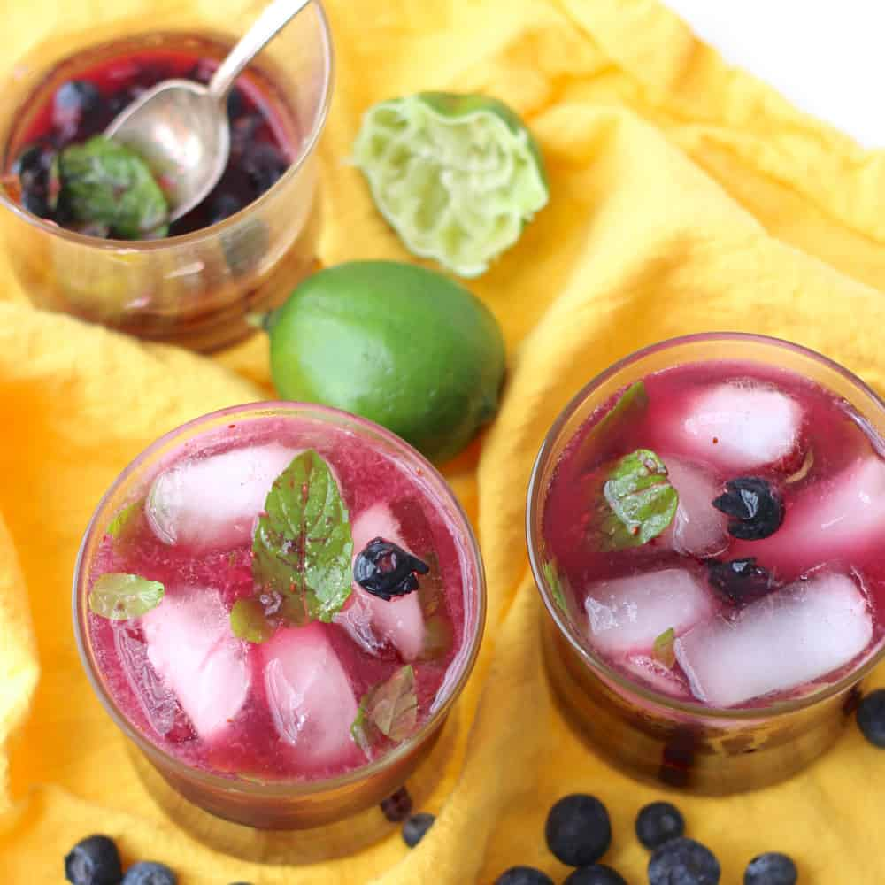 Juicy blueberries, muddled mint, fresh squeezed lime juice, a dash of sugar, club soda, and rum make this fabulous warm weather drink ~ Blueberry Mojitos from Living Well Kitchen