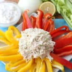 scoop of chicken salad on top on yellow and red bell peppers on a white plate with cottage cheese, onion, lemon and celery